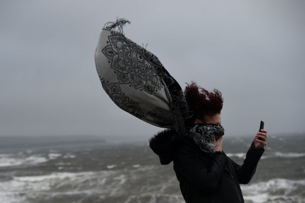 A woman takes a picture during storm Ophelia in the County Clare town of Lahinch, Ireland October 16, 2017.