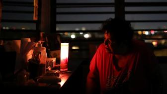 Carmen Correa uses a candle to light up a room at the Moradas Las Teresas Elderly House, where about two hundred elderly people live without electricity following damages caused by Hurricane Maria in Carolina, Puerto Rico, September 30, 2017.  REUTERS/Carlos Barria