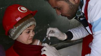 A member of the Syrian Arab Red Crescent administers a vaccination to a girl at a school in the rebel held Douma neighborhood of Damascus, Syria March 21, 2016. REUTERS/Bassam Khabieh      TPX IMAGES OF THE DAY