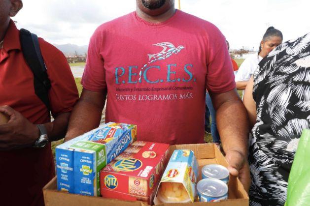 Los habitantes de la isla colaboran con la ONG P.E.C.E.S. en Humacao, Puerto Rico, para la distribución...