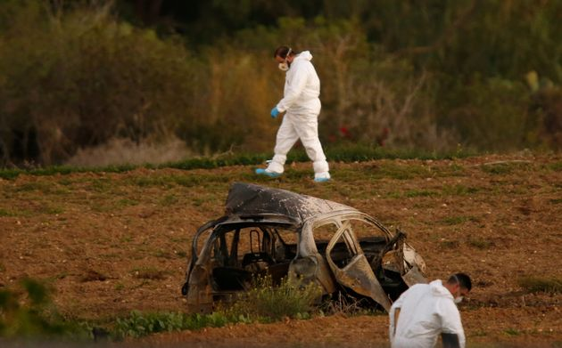 Forensic experts walk in a field after a powerful bomb blew up a car and killed investigative journalist...