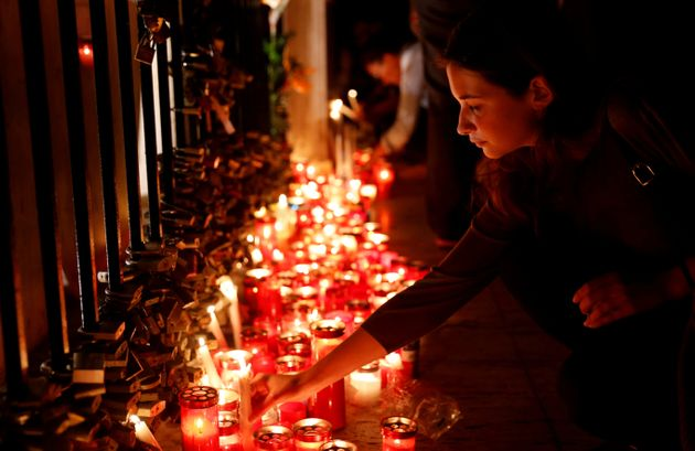 A woman places a candle on the Love monument during a silent candlelight vigil for Daphne Caruana Galizia.