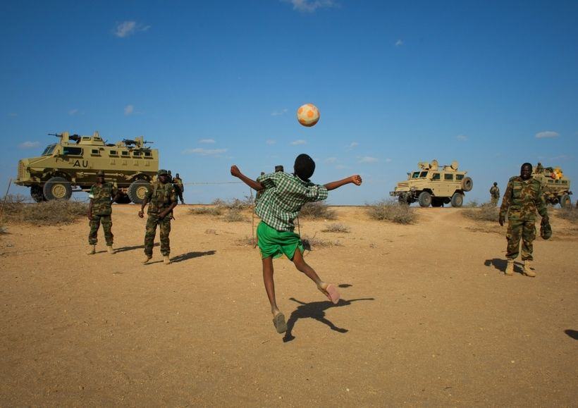 <em>Ugandan soldiers deployed with AMISOM play football with Somali children after taking back a town from al-Shabab. </em>