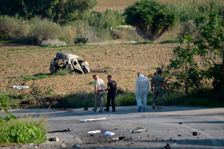 Police and forensic experts inspect the wreckage of a car bomb believed to have killed Caruana Galizia