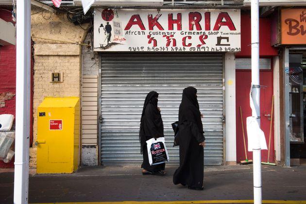 Two muslim women walk past an African clothes store in Shepherd's Bush market in west London. A surge...