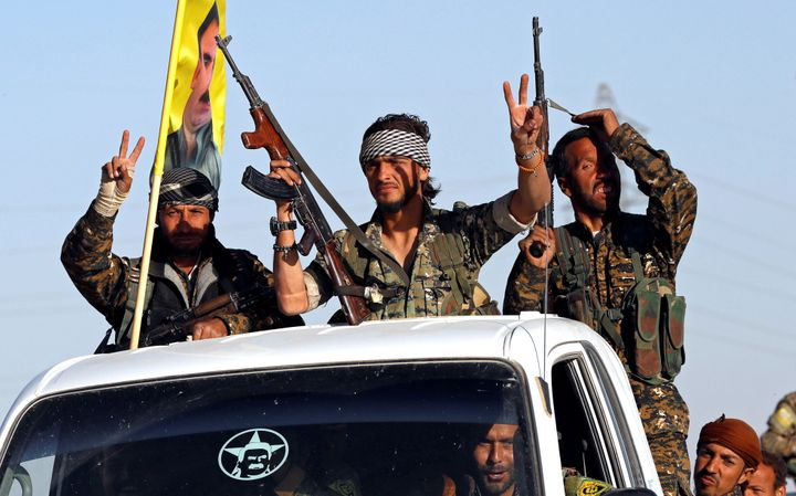 Fighters of Syrian Democratic Forces make the V-sign as their convoy passes in Ain Issa, Syria October 16, 2017.
