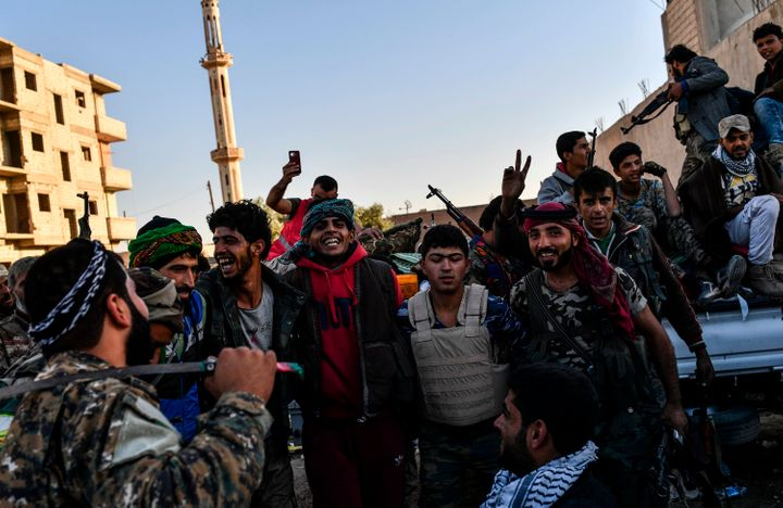 Members of the Syrian Democratic Forces (SDF), backed by US special forces, celebrate at the frontline in the Islamic State (