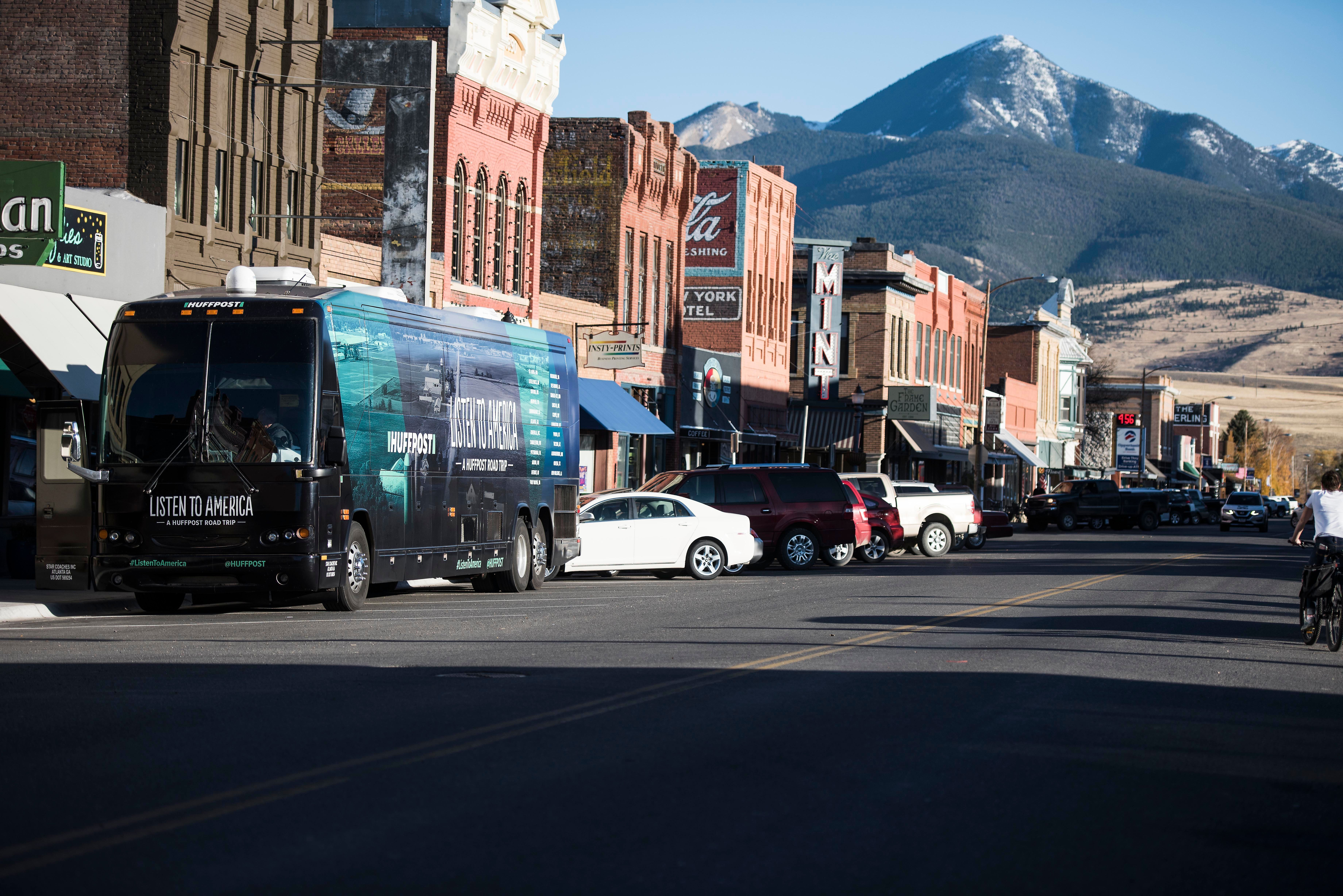 """LIVINGSTON, MT - OCTOBER 16: The tour bus sits in front of the city skyline during HuffPost's visit to Livingston, Montana, on Oct. 16, 2017, as part of """"Listen To America: A HuffPost Road Trip."""" The outlet will visit more than 20 cities on its tour across the country. (Photo by Damon Dahlen/HuffPost) *** Local Caption ***"""