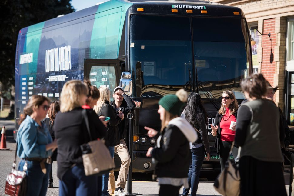 Pedestrians visit the HuffPost bus.