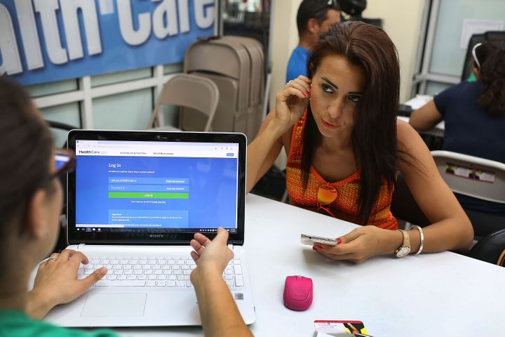 Alina Nurieva, right, picks an insurance plan available in the third year of the Affordable Care Act at a store set up in Miami's Mall of the Americas on Nov. 2, 2015.