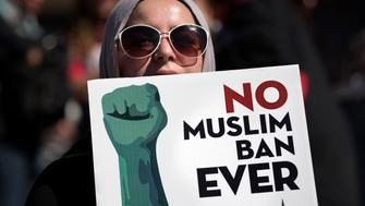 An activist holds a sign during a protest against President Trump's travel ban in Los Angeles, California on October 15, 2017. The No Muslim Ban Ever rally was organized by the Council on American-Islamic Relations in response to the Trump administrations third iteration of the of the travel ban. (Photo by: Ronen Tivony) (Photo by Ronen Tivony/NurPhoto via Getty Images)