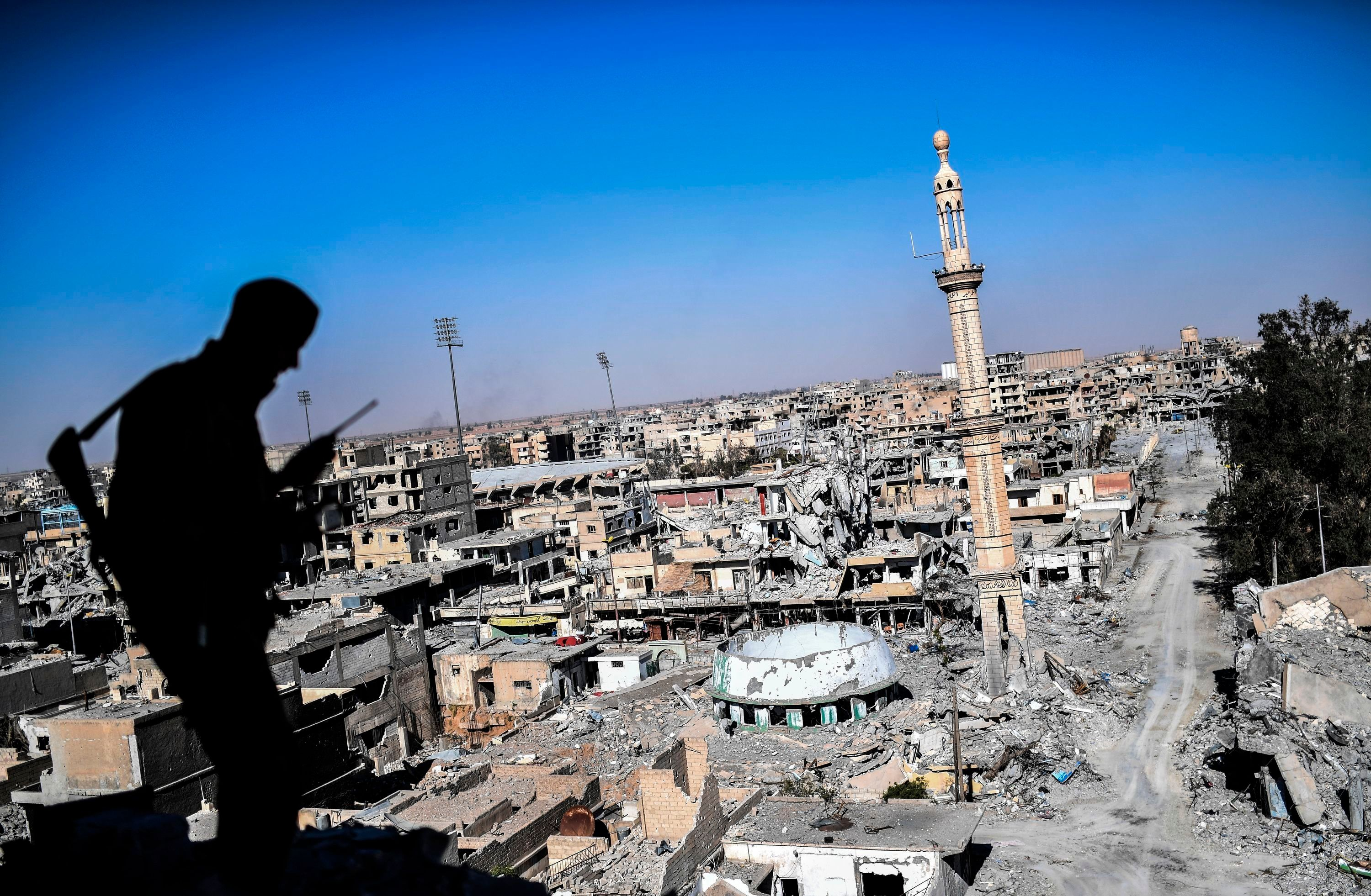 A member of the Syrian Democratic Forces, backed by U.S. Special Forces, talks on the radio near Raqqa's...