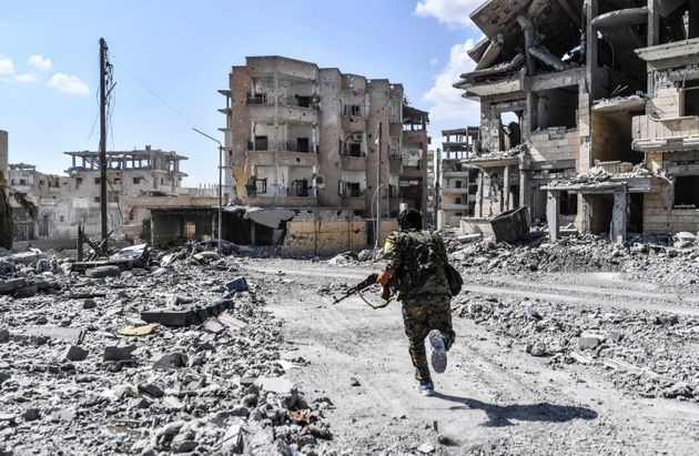 A member of the Syrian Democratic Forces takes cover from sniper shots near the central hospital of Raqqa...