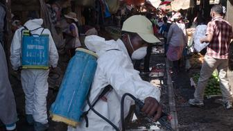 Council workers spray disinfectant during the clean-up of the market of Anosibe in the Anosibe district, one of the most unsalubrious districts of Antananarivo on October 10, 2017. The World Health Organization has warned that a deadly outbreak of the plague, which began in late August, has claimed more than 20 lives in Madagascar and is swiftly spreading in cities across the country. Rats are porters of fleas which spread the bubonic plague and are attracted by garbages and unsalubrity. Pneumonic plague, which is passed through person-to-person transmission, has also been recorded. / AFP PHOTO / RIJASOLO        (Photo credit should read RIJASOLO/AFP/Getty Images)