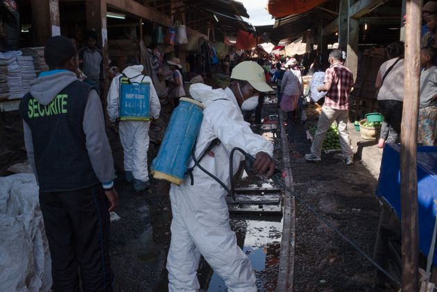 Governmentworkers spray disinfectant duringcleanup ofa marketin Antananarivo,...
