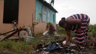 A woman searches for useable goods amidst broken items as a neighbor tries to fix the roof of her home, after the island was hit by Hurricane Maria in Toa Baja, Puerto Rico October 16, 2017. REUTERS/Alvin Baez