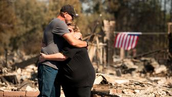 Charlie and Kate Higgins embrace in front of their burned home in Santa Rosa, California on October 12, 2017.  Hundreds of people are still missing in massive wildfires which have swept through California killing at least 26 people and damaging thousands of homes, businesses and other buildings. / AFP PHOTO / JOSH EDELSON        (Photo credit should read JOSH EDELSON/AFP/Getty Images)