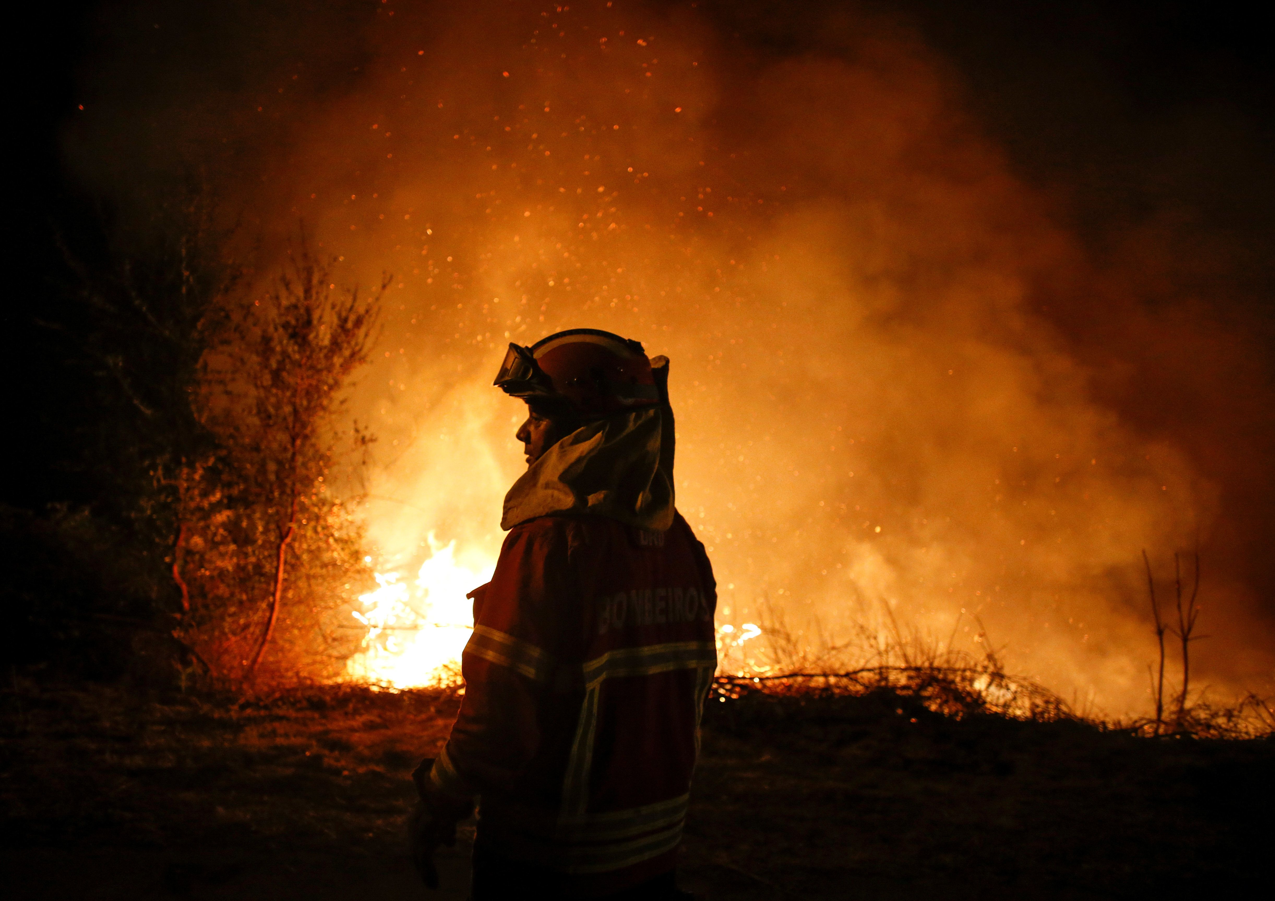 A firefighterstandssilhouetted againstthe flames in Cabanoes near Lousa, Portugal,...