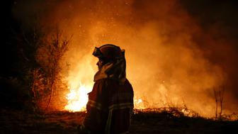 A firefighter is seen near flames from a forest fire in Cabanoes near Lousa, Portugal,  October 16, 2017.  REUTERS/Pedro Nunes