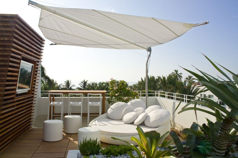 Luxe white daybeds scatter the roof next to the pool and overlook the ocean beyond. Brilliant way to watch the sun go down wi