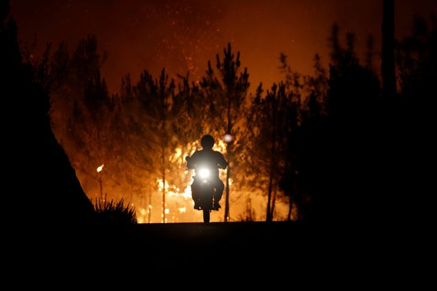 A firefighter rides a motorbike away from the firearoundthe village of Macao, near Castelo...