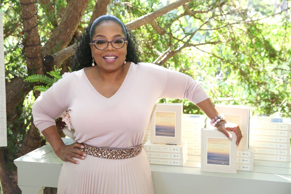 "Oprah poses beside her newest book, ""The Wisdom of Sundays."""