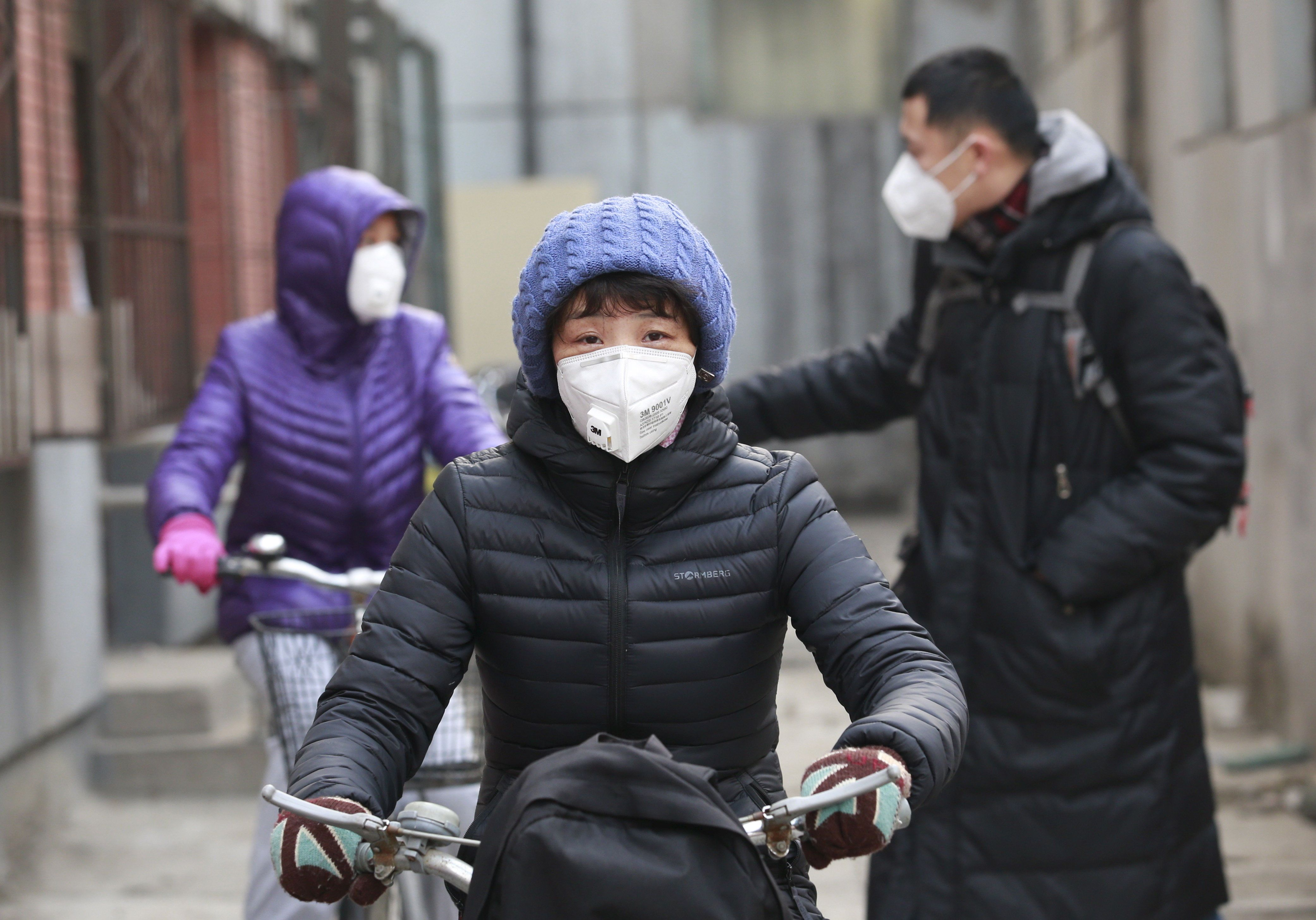 "Jiang Zhen's family, wearing protective masks, ride bicycles as they head to a children's boarding school, on the second day after China's capital Beijing issued its second ever ""red alert"" for air pollution, in Beijing, China, December 20, 2015. To match CHINA-POLLUTION/BUBBLE   REUTERS/Kim Kyung-Hoon"