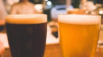 Two glasses of craft beer resting on a rustic wooden bar, one dark one amber. Looks like a great beer tasting session.