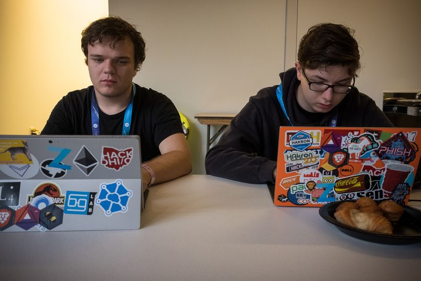 Two developers write code during the ETHWaterloo Hackathon.