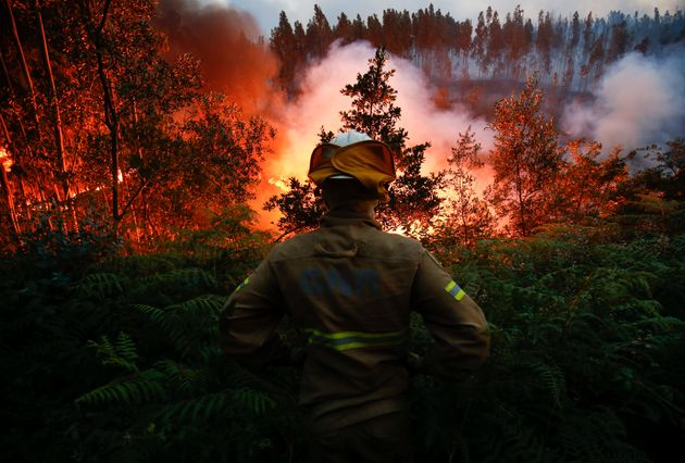 A firefighter watches ablaze near the village of Fato in central Portugal on June 18,