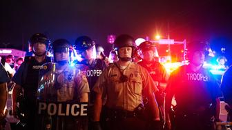 St. Louis County Police and Missouri State Highway Patrol troopers stand guard as protesters march on West Florissant Avenue in Ferguson, Missouri on August 9, 2015.  A day of peaceful remembrance marking the anniversary of 18-year-old black teen Michael Brown's killing by police in the US city of Ferguson came to a violent end on August 9 as gunfire left at least one protester injured.       AFP PHOTO / MICHAEL B. THOMAS        (Photo credit should read Michael B. Thomas/AFP/Getty Images)