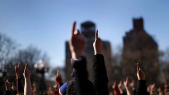"Women raise one finger to the air as they dance to the theme song of the ""One Billion Rising"" campaign in New York City's Washington Square Park as the clock strikes 2:14EST on Valentines Day February 14, 2013. ""One Billion Rising"" is a campaign aimed to call an end to violence against women and girls. This date marks the 15th Anniversary of when V-Day was founded by award-winning playwright Eve Ensler and the One Billion Rising campaign is based on the statistic that 1 in 3 women will be beaten or raped in her lifetime according to organizers. REUTERS/Mike Segar   (UNITED STATES - Tags: SOCIETY CIVIL UNREST)"