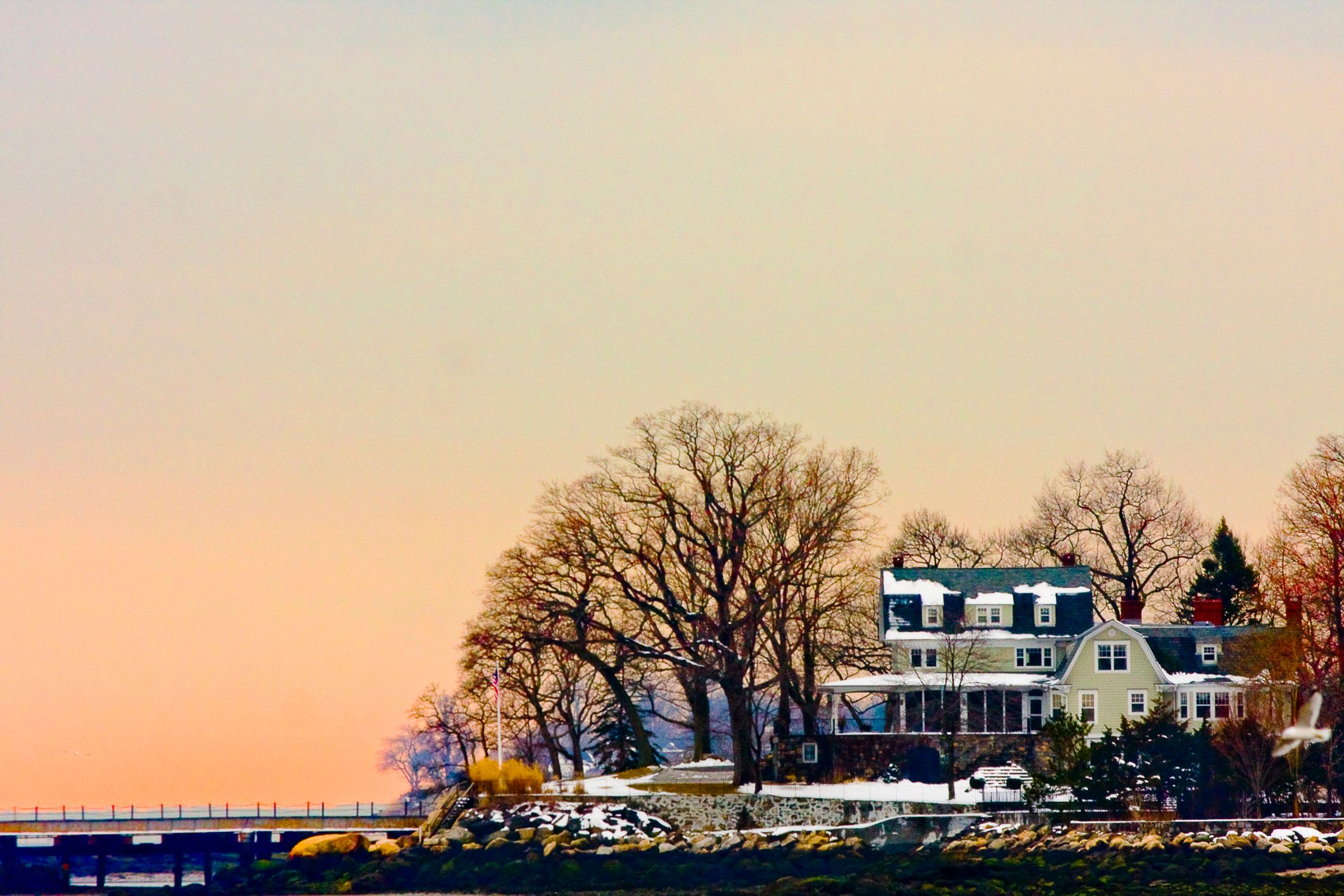 A New England style house in Stamford, CT overlooks the Long Island Sound in winter time.