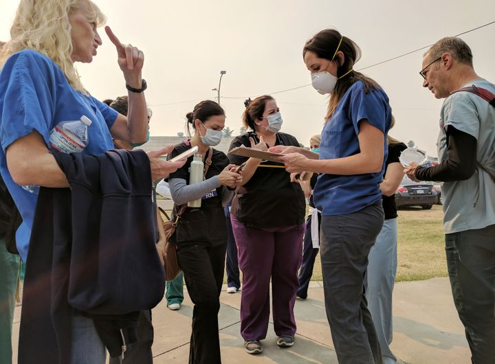 Volunteer nurses wear protective masks due to smoke from burning wildfires as they receive instructions at a shelter in Petal