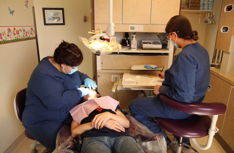 Dental Therapists, Elsie Pelawook and Savannah Bonorden, performing dental work on a patient.