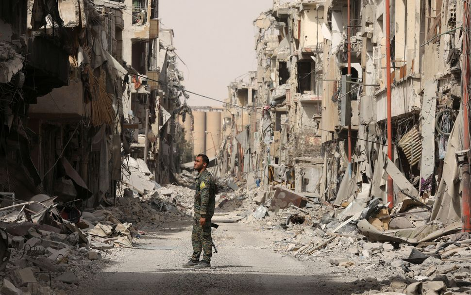 A fighter from the Syrian Democratic Forces (SDF) stands next to debris of damaged buildings in Raqqa, Syria, on Sept. 25, 20