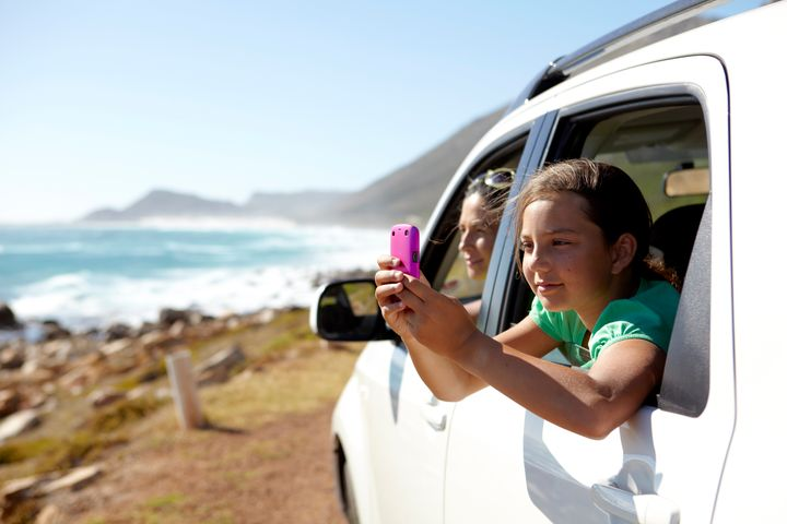 Girl, aged 9, taking a picture of a sea view from a car window Alistair Berg via Getty Images