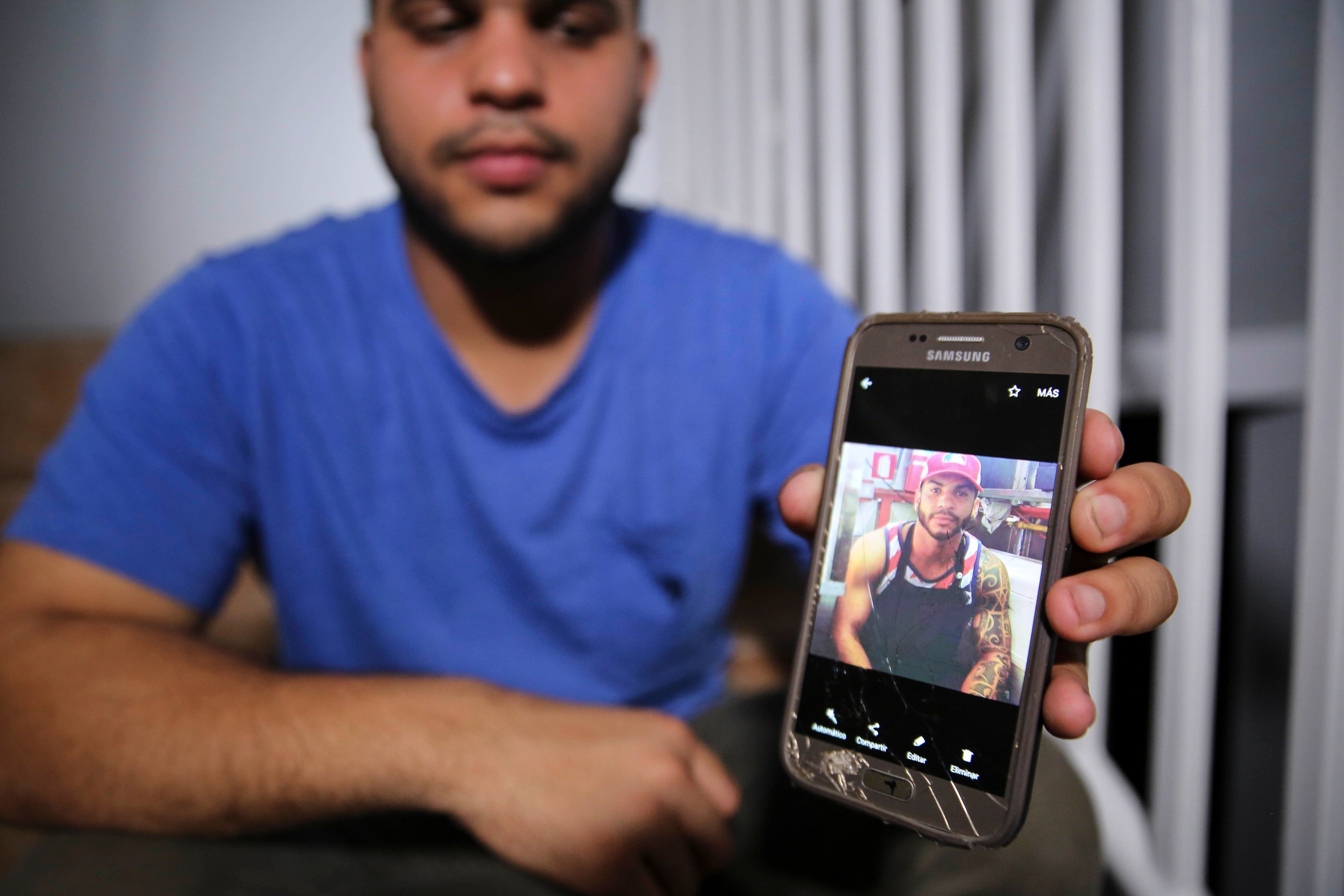 Christian Romero shows HuffPosta photo of his late brother Romsy on Oct. 14, 2017.The family says doctors believe
