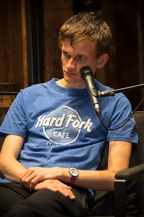 Vitalik Buterin rests his head on a microphone while answering questions during a panel discussion.