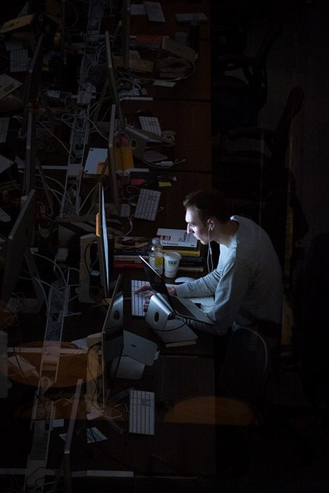 A lone hacker writes code in the dark on his computer as light from his monitor shines upon his face.