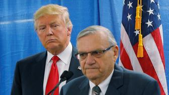 FILE PHOTO: U.S. Republican presidential candidate Donald Trump listens as Maricopa County Sheriff Joe Arpaio (R) speaks to reporters before a campaign rally in Marshalltown, Iowa January 26, 2016.  REUTERS/Brian Snyder/File Photo