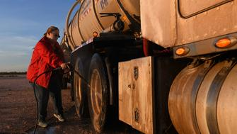 Tara Smith washes one of the rigs parked in the truck yard west of Odessa.