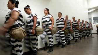 Maricopa County female inmates march for chain gang duty in Phoenix, Arizona October 21, 2003.  The women are padlocked together by the ankle and marched military style  to a van to be transported to their work site. The women volunteer for chain gang duty to get out of lockdown , where four prisoners are shut in a cell 8 x 12 feet wide 23 hours  day. If they spend 30 days on the chain gang , picking up trash, weeding or burying bodies, they can get out of the punishment cell.