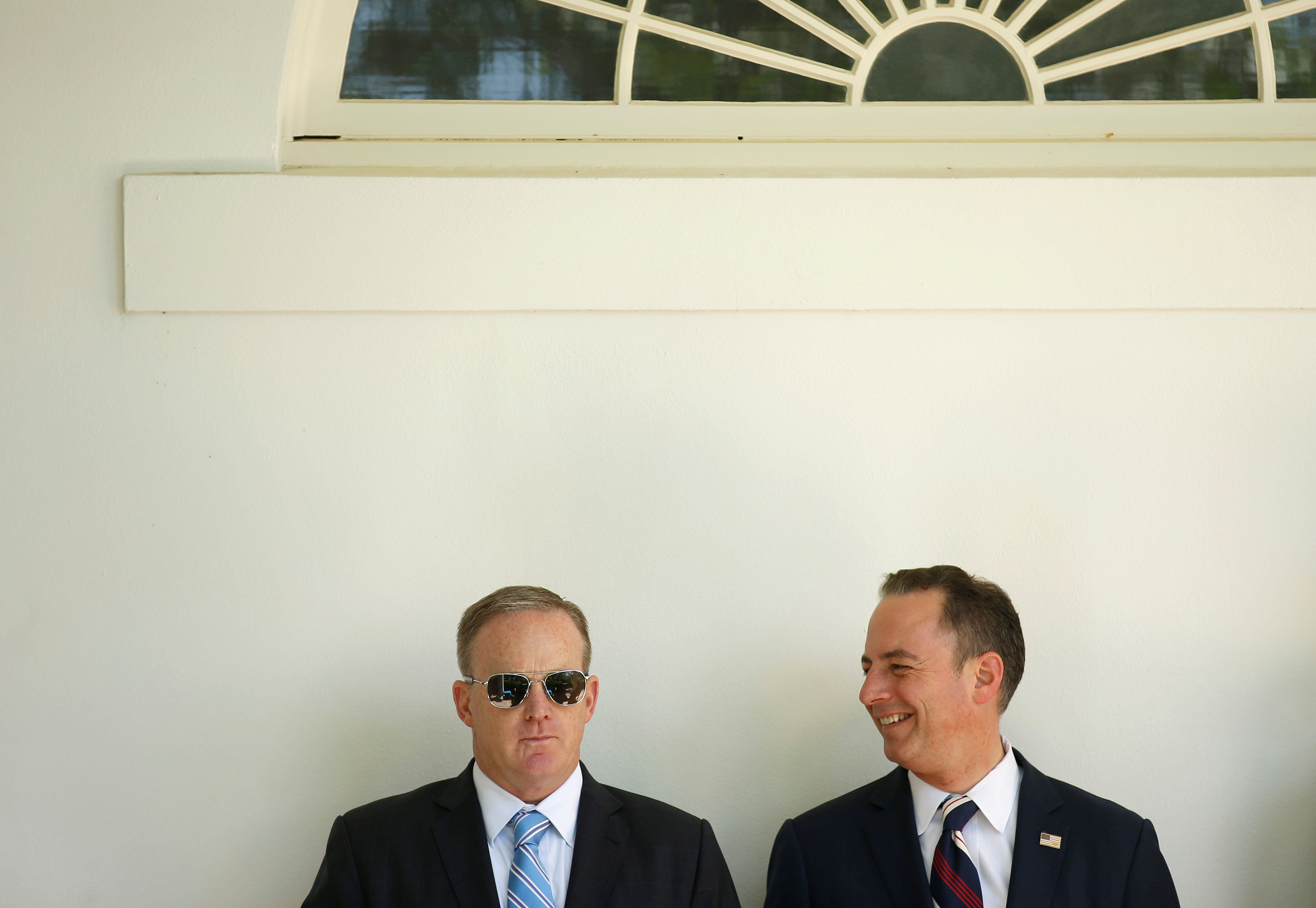 White House Press Secretary Sean Spicer (L) and White House Chief of Staff Reince Priebus watch as U.S. President Donald Trump presents the U.S. Air Force Academy football team with the Commander-in-Chief trophy in the Rose Garden of the White House in Washington, U.S., May 2, 2017. REUTERS/Joshua Roberts