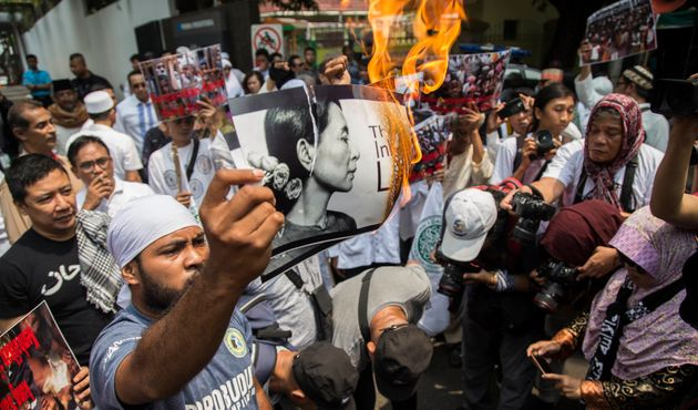 An Indonesian protester burns a picture of Suu Kyi during a rally in front of the Myanmar embassy in...