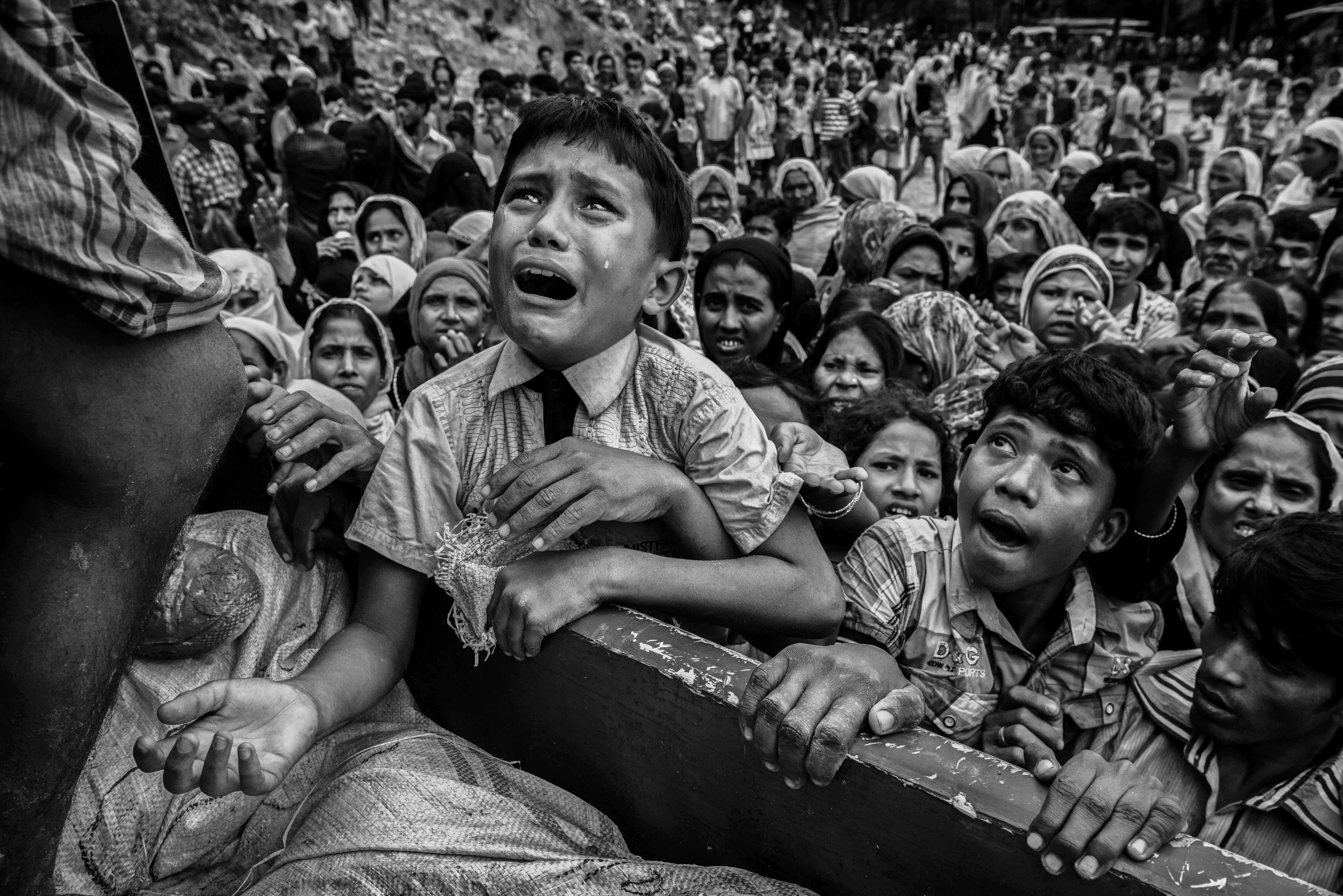 A Rohingya refugee boy desperate for aid cries as he climbs on a truck distributing aid for a local NGO...