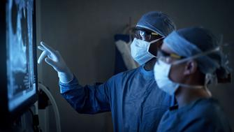 Shot of two surgeons analyzing a patient's medical scans during surgery