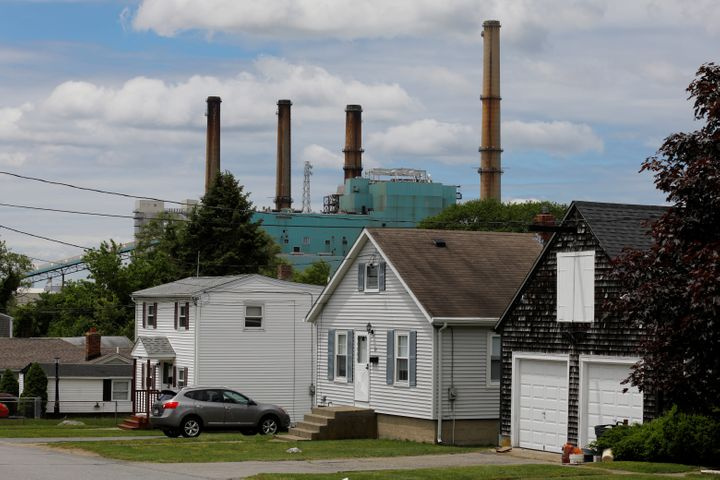 The Brayton Point power plant, a coal-fired power plant that was shut down June 1, rises behind houses in Some
