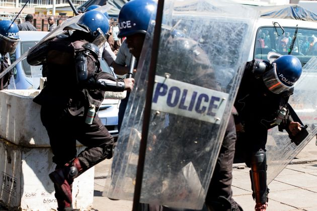 Police surround an activist lying on the ground at Harare Central Police Station during a protest in...