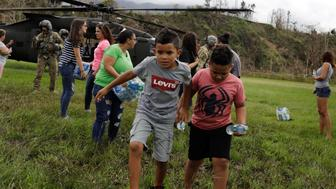 "Boys carry water away from an HH-60 Blackhawk helicopter after soldiers working with the U.S. Army's 101st Airborne Division's ""Dustoff"" unit dropped off relief supplies during recovery efforts following Hurricane Maria, in Jayuya, Puerto Rico, October 5, 2017. REUTERS/Lucas Jackson  SEARCH ""JACKSON TIRADO"" FOR THIS STORY. SEARCH ""WIDER IMAGE"" FOR ALL STORIES."